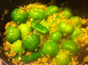 Adding the tomatilos to the saucepan.