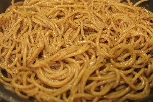 The pasta coated with the oil and pepper. It has absorbed most of the water at this point.