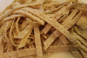 Tortilla strips. Be sure to use a very sharp knife so you can get even strips without tearing up the tortillas.